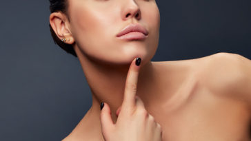 Close-up lips, neck and shoulder of young girl, touching her chic over grey background